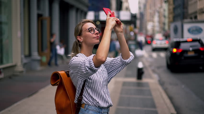 Millennial hipster girl tourist in casual outfit photographing buildings architecture and in New York using camera and application on modern cellular phone, slow motion effect. Female wanderlust