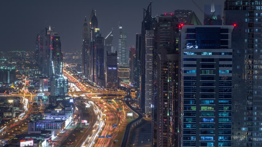 Aerial view to skyscrapers on Dubai downtown and Sheikh Zayed road night timelapse, Dubai, United Arab Emirates. Modern towers and evening traffic on highway #1027370189