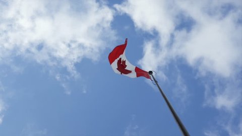 Canadian flag flying & waving in a cloudy blue sky, in slow motion