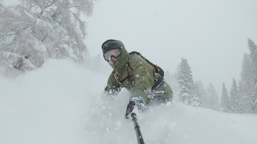 ACTION: A snowboarder rides through deep snow and turns in the fresh powder. Snow splashes into the camera and athlete. Winter sports activities. | Shutterstock HD Video #1027390175