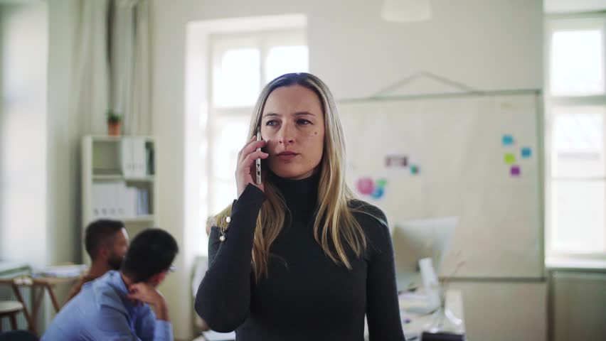 Young businesswoman with smartphone working in a modern office. | Shutterstock HD Video #1027412969