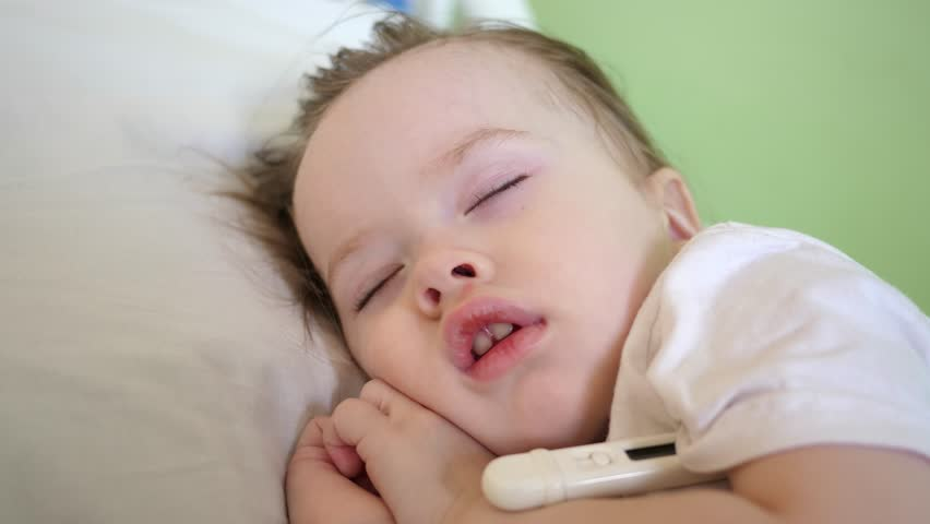 Sick kid in bed with a thermometer. the child is sick mom pities the baby. mother next to a sick daughter, the child has fever. Mom cares for the sick child. little girl in the children's hospital
