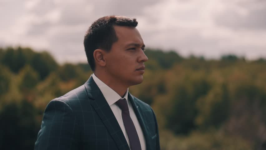 A young guy stands in the background of the forest and looks into the distance. Handsome guy. Beautiful scenery. Serious look. Close up. | Shutterstock HD Video #1027415240