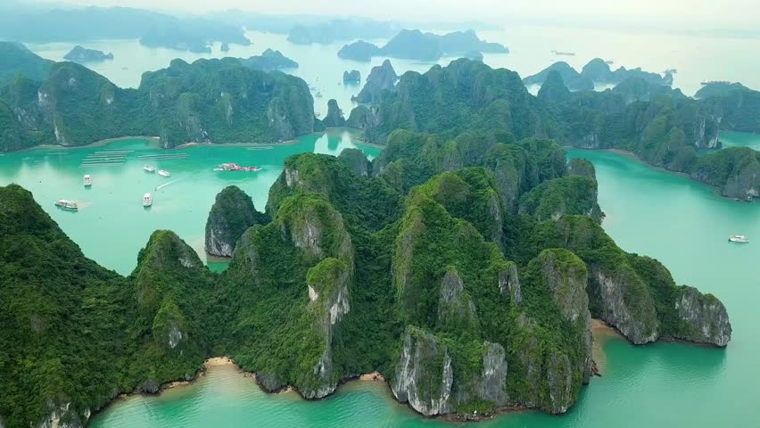 Unique aerial drone flight over natural rocks green tops Halong bay islands from sea blue azure water. Wild natural untouched seascape. Asia Vietnam. Best Travel sight.