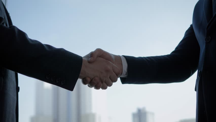 Close up of the hands of top managers in business suits, shake hands with each other, against the window in the office, agree to a deal or say hello. Slow motion, unrecognizable person | Shutterstock HD Video #1027433285