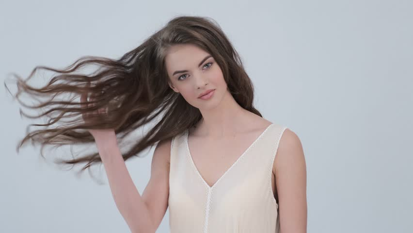 Beautiful woman with long curly brown hair. Fashion model looks to the camera at studio. Closeup face of an attractive brunette woman. Sexy model with a saexy look. 4k footage. Slow motion.  | Shutterstock HD Video #1027433714