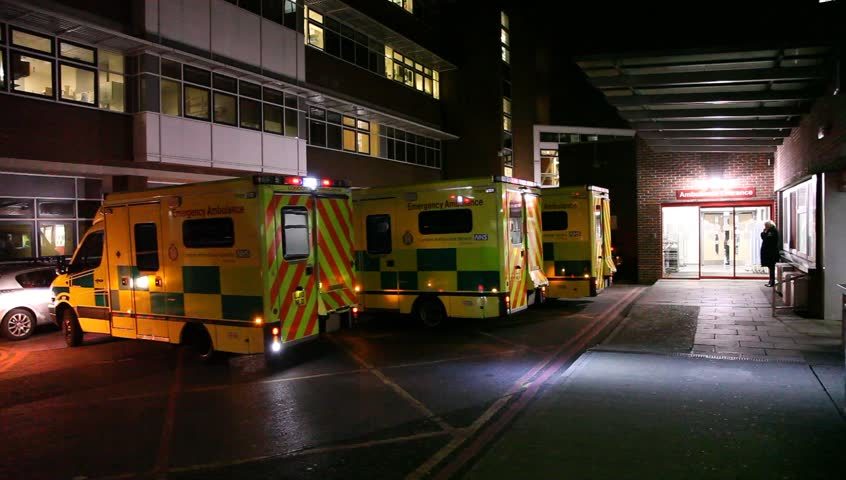 LONDON, UK - 2019: NHS A and E exterior ambulance arrives night handheld