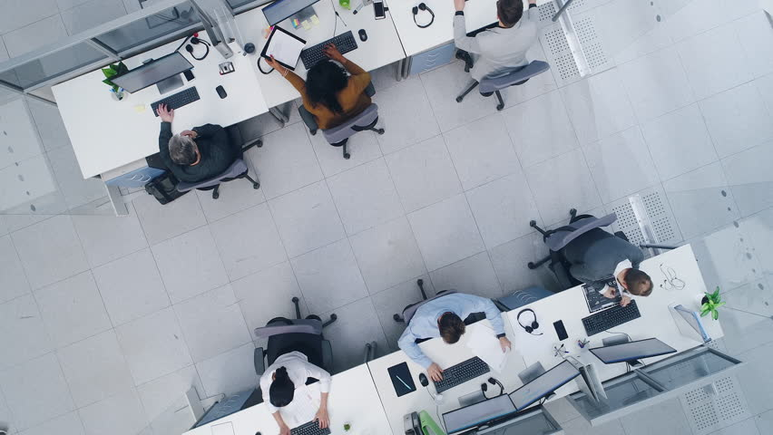 Aerial Top Down Drone Shot of Big Busy Corporate Office with Tow Rows off Businessmen and Businesswomen Working on Desktop Computers. Bright Open Space Office with Businesspeople and Salespeople