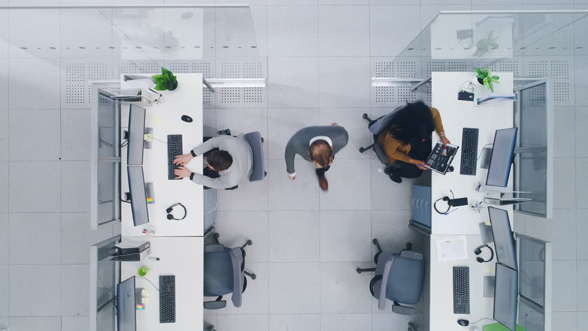 Aerial Top Down Drone Shot of Big Busy Corporate Office with Tow Rows off Businessmen and Businesswomen Working on Desktop Computers. Bright Open Space Office with Businesspeople and Salespeople | Shutterstock HD Video #1027450481