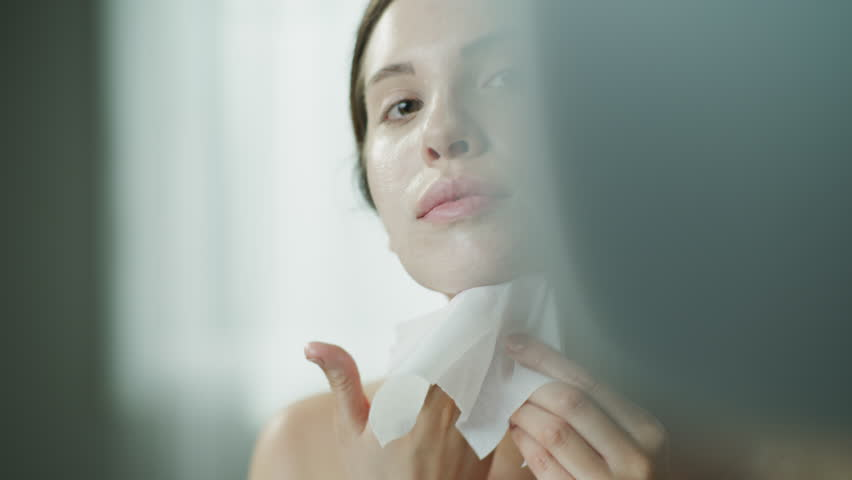 Close up of woman rubbing moisturizer on face with washcloth in mirror / Cedar Hills, Utah, United States