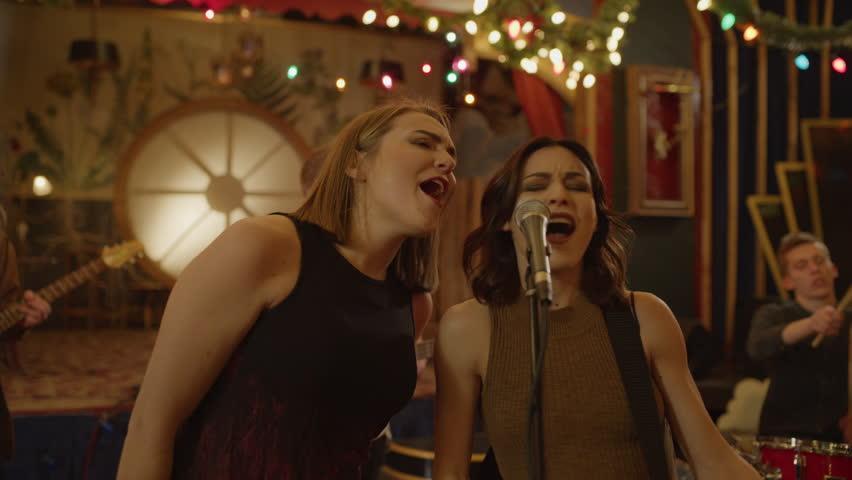 Panning shot of women singing duet in band rehearsing in nightclub / Provo, Utah, United States