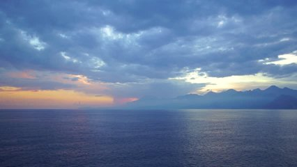 Aerial top view of peaceful calm dark blue sea water surface, cloudy sunset or sunrise sky and silhouettes of mountains. Real time 4k video footage.