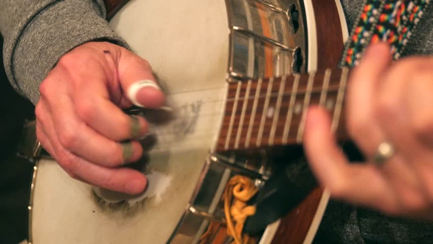 A musician picking the banjo to bluegrass music
