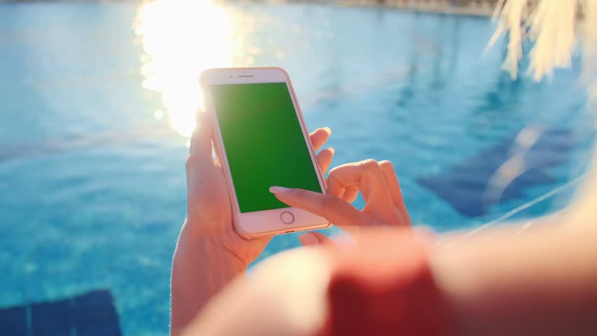 Barcelona, Spain - March 11 2019: Close up of girl using mobile phone green screen while relaxing near the swimming pool. Hands holding smartphone chrome key, tapping modern display smart phone.