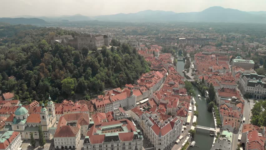Scenic old city center with a medieval castle on a hill and a river flowing by with mountains in the background, aerial, wide angle view Royalty-Free Stock Footage #1027477445