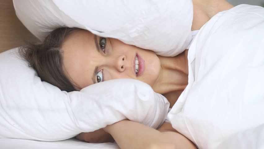 Young irritated woman trying to sleep annoyed by bad noisy room neighbors covering ears with pillow, angry girl student disturbed with loud noise problem wake up lying in bed suffer from insomnia | Shutterstock HD Video #1027488356