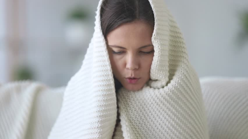 Covered with plaid young woman freezing feeling cold at home no central heating problem concept, ill sick girl having fever flu influenza temperature symptoms wrapped in blanket shivering indoors