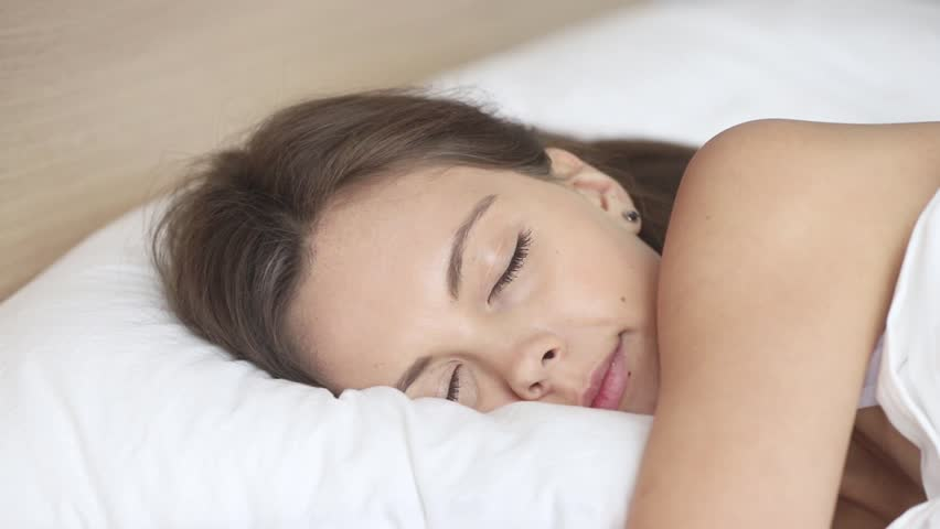 Calm young woman sleeping well in comfortable cozy fresh bed on soft pillow white linen orthopedic mattress, peaceful serene girl resting lying asleep enjoying healthy good sleep nap in the morning | Shutterstock HD Video #1027488380