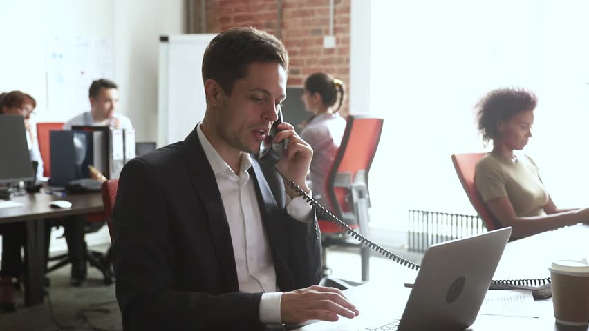 Male broker sales manager worker in suit talking on the phone using laptop at work desk, serious businessman employee making telephone call consulting customer in modern office at corporate workplace Royalty-Free Stock Footage #1027488404