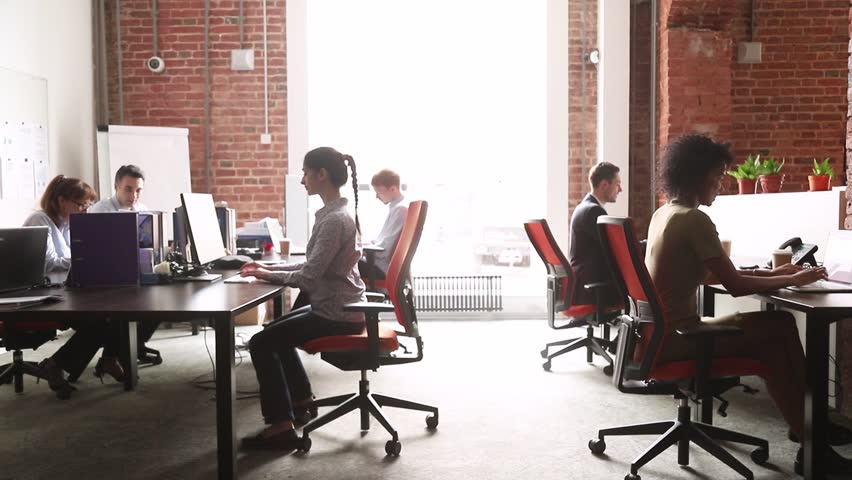 Modern corporate office open space with multicultural busy staff employees group using pc computers sitting at desks in work room interior, diverse company team people workers in coworking enterprise