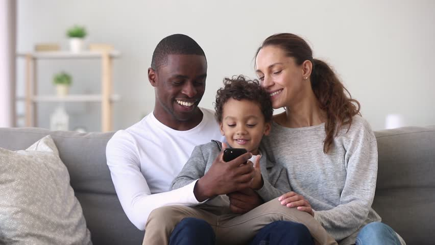 Happy mixed ethnicity family little african dad kid son and caucasian mom holding phone having fun with smartphone, mother father with child boy looking at cellphone enjoy using mobile apps at home