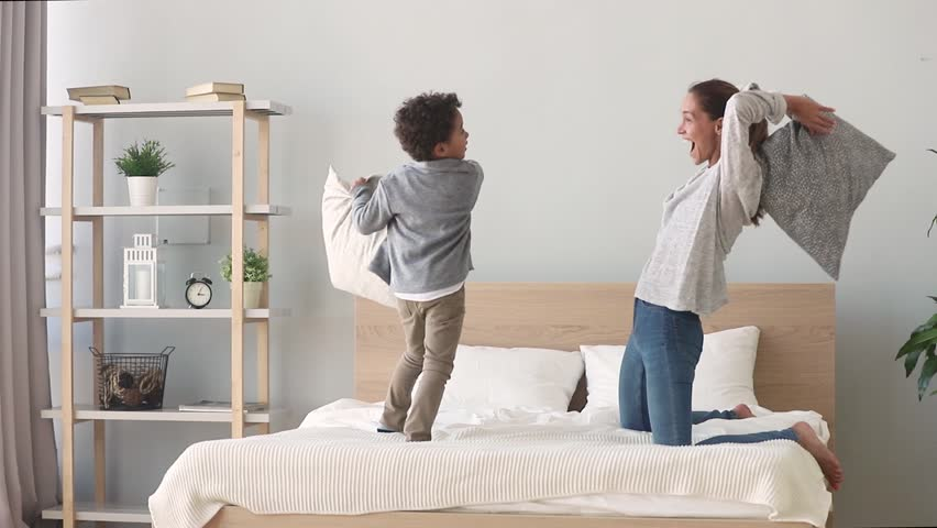 Happy african american mixed race family mom baby sitter and little son having fun pillow fight on bed, young mother nanny laughing playing funny game with small child boy in bedroom on leisure time