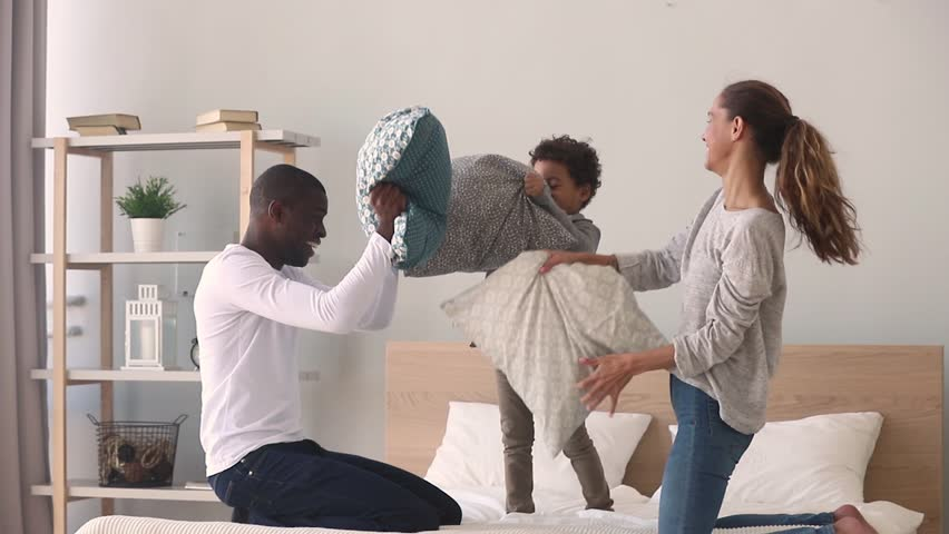 Happy mixed ethnicity family mom african dad and little kid son having fun pillow fight on bed, young interracial mother father child boy laughing feel joy play funny game in bedroom leisure activity