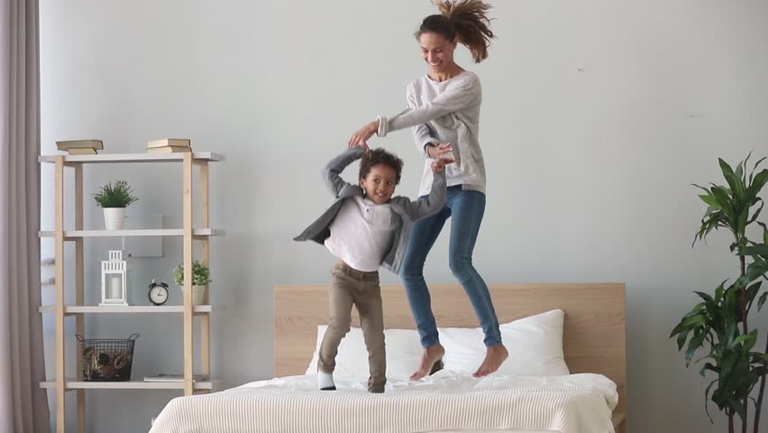 Happy family african american mixed race kid boy and caucasian mom baby sitter holding hands jumping on bed, young mother having fun laughing playing funny active game with cute child son in bedroom