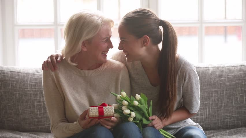 Loving adult daughter presenting spring flowers and gift box to happy old mother laughing bonding embracing, young woman congratulating hugging senior mom looking at camera on mothers day at home Royalty-Free Stock Footage #1027488542