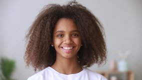 Pretty african american teen school girl looking at camera, adolescent funny mixed race teenage model with afro hair and beautiful face toothy smile posing at home, happy black teenager, portrait
