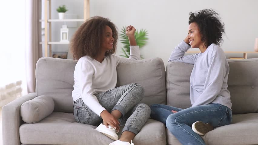 Happy best friends african mother and teen daughter talking sitting on sofa at home, friendly black family loving mum with teenager girl chatting on couch share secrets having fun trust conversation
