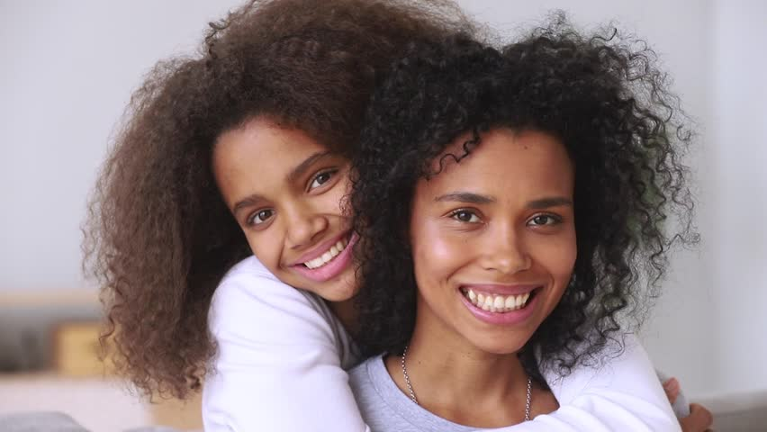 Affectionate happy african american family single mother and teen girl embracing, smiling mixed-race teenage girl hugging mom from behind looking at camera, mum child love warm relationship, portrait