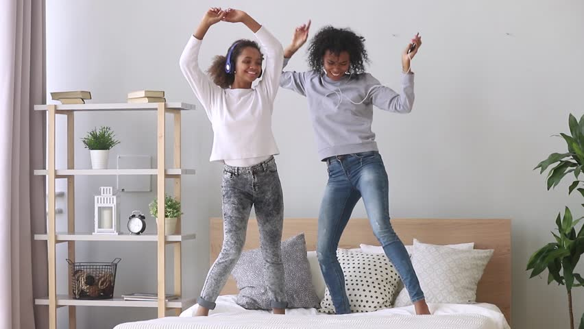 Happy carefree family black mom and teen daughter wearing headphones dancing on bed listening to music on phone, funny funky african american mother sister and teenager girl having fun in bedroom