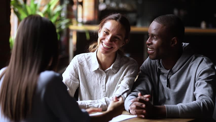Happy interracial couple customers sign loan investment contract make real estate insurance mortgage deal meeting agent broker, mixed ethnicity family clients handshake realtor buy rent new house Royalty-Free Stock Footage #1027488641