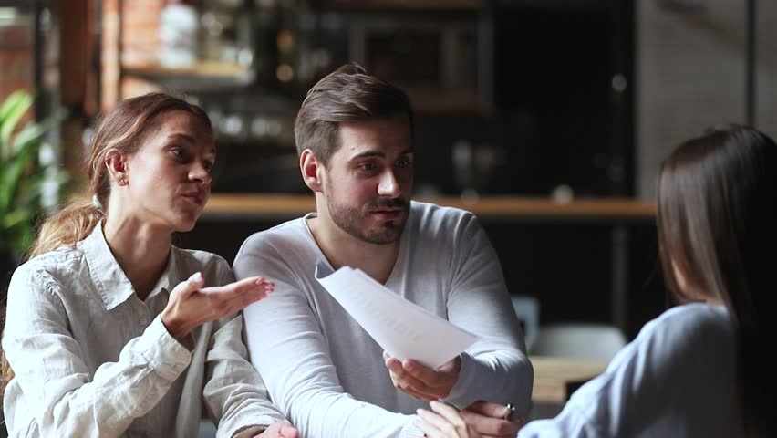 Annoyed angry young couple customers clients holding papers arguing with manager having complaint on bad contract service demand claim insurance compensation meeting lawyer on legal fraud fight | Shutterstock HD Video #1027488644
