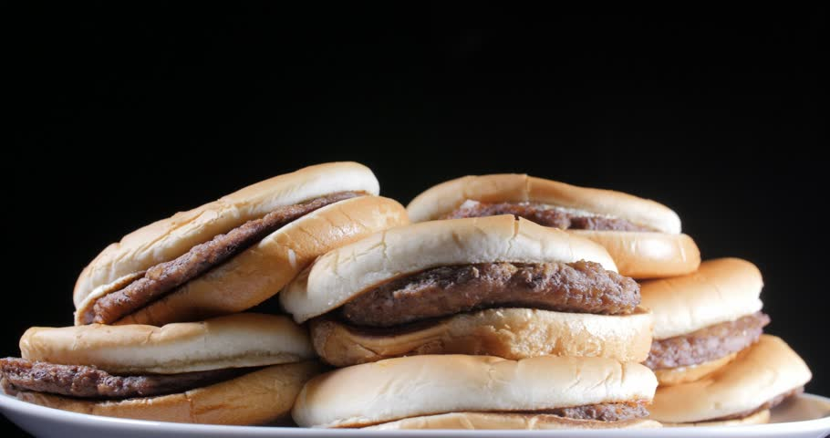 Rotating view of heaped plain beef patty burgers on flat buns stacked on a plate over a black background | Shutterstock HD Video #1027491872