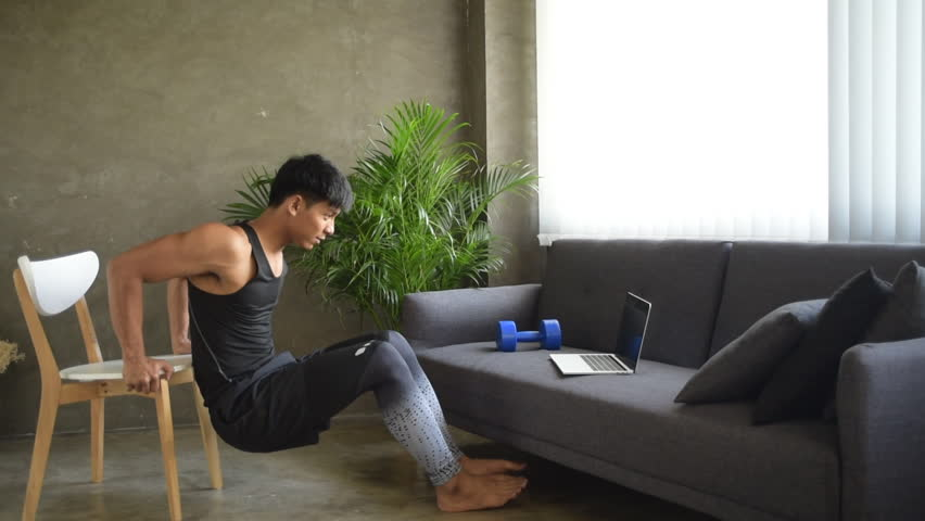 The handsome man learning how to stretching body from laptop and doing,exercise at home,for weight lost and built muscle #1027501133