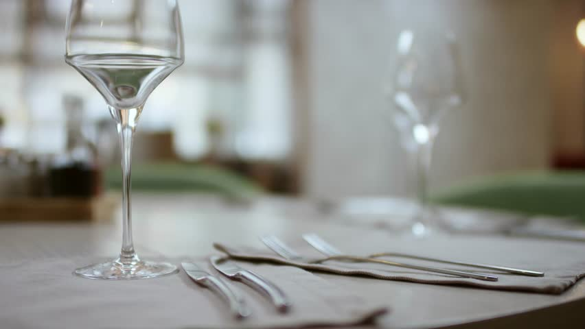 The waiter serves the table in the cafe. Video from the restaurant. The waiter straightens the knife on the table. Table setting. Preparing the restaurant for the opening. decorated table for a dinner