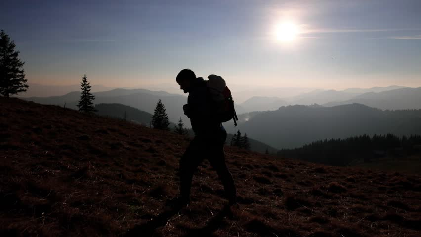 man hiking on the edge of the mountain as a silhouette in sunset #1027517588