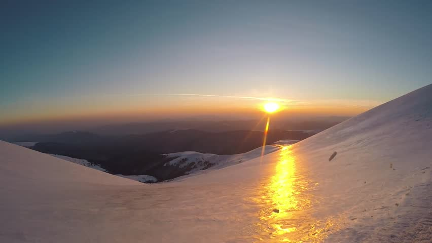 Climbimg on the snow mountain hills. Sunset on the mountains. Winter mountain view. Going up the hill. Clear blue sky. Top of the mountain. Sunset in winter.  | Shutterstock HD Video #1027547456