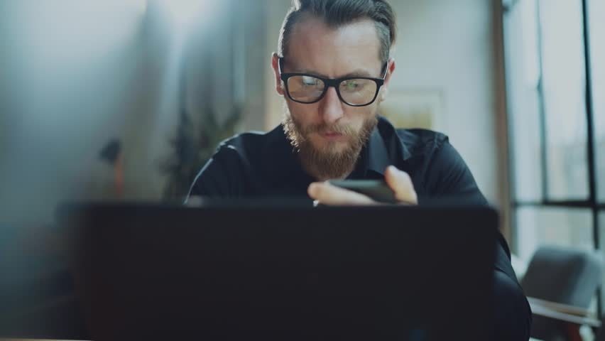 Confident businessman working at sunny office on desktop computer while sitting at the table.