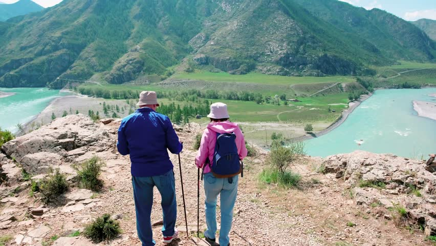 Two elderly tourists admire the view of the river and mountains from a height | Shutterstock HD Video #1027552403