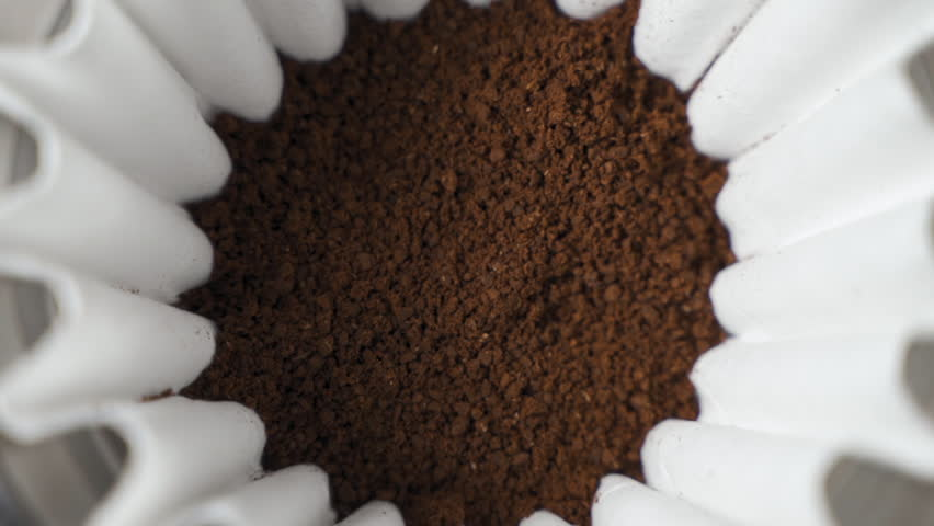 Hot water pour over into ground coffee beans close up slow motion | Shutterstock HD Video #1027576904