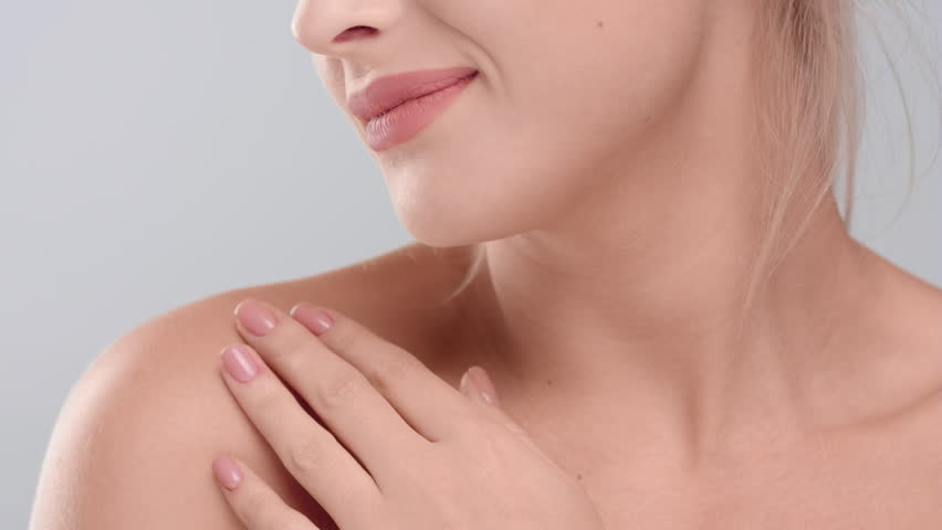Close-up beauty portrait of young woman touching her smooth skin in collarbone area against grey background | skin care concept | Shutterstock HD Video #1027606118