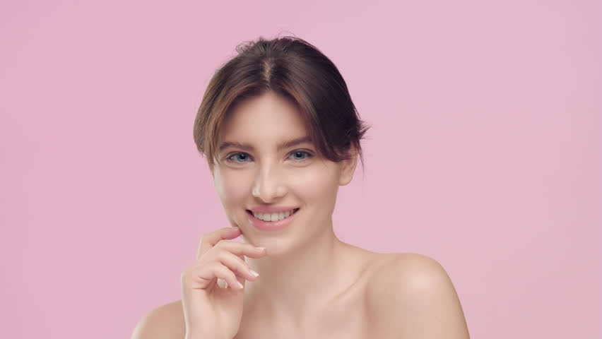 Close-up beauty portrait of young pretty brunette Caucasian woman with smooth healthy skin and nude make-up strokes her smooth skin with pleasure, looks at camera and smiles | Skincare concept | Shutterstock HD Video #1027606262