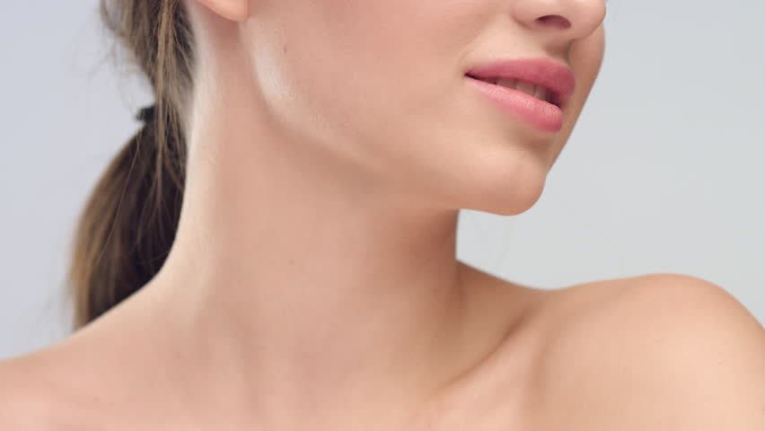 Close-up beauty portrait of young brunette woman with smooth healthy skin and bare shoulders, she smiles on light grey background | Skincare concept. | Shutterstock HD Video #1027606280