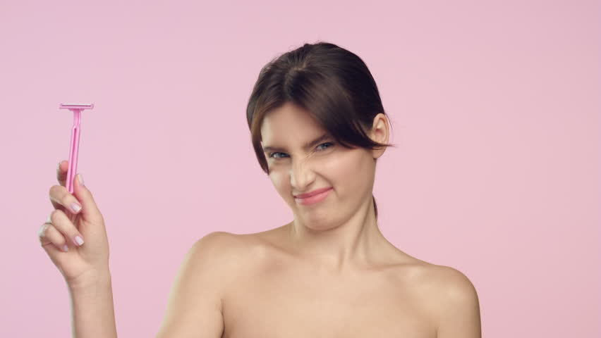 Medium close-up beauty portrait of young brunette Caucasian woman throws out women shaver and smiles against a light pink background | Laser treatment for unwanted hair concept