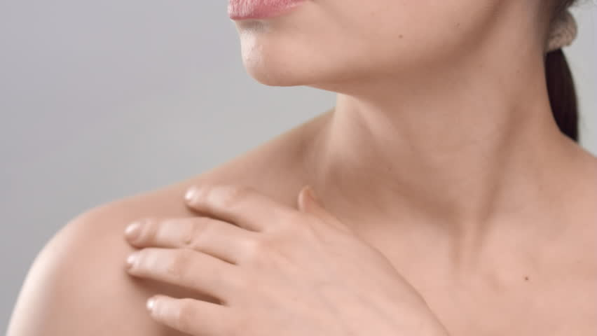 Close-up beauty portrait of young adult woman, that gently strokes her clavicles on light grey background | Skincare concept | Shutterstock HD Video #1027606619