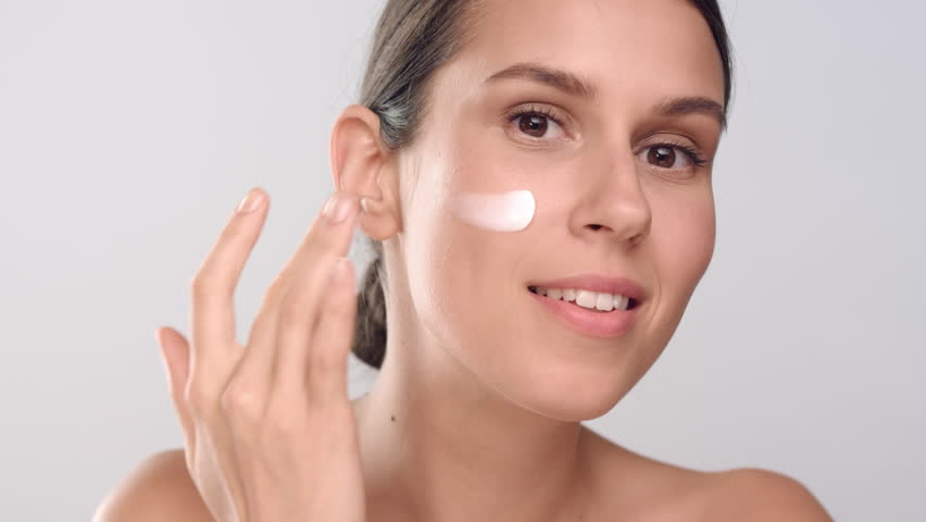 Close-up beauty portrait of young positive brown-haired Caucasian woman with perfect smooth healthy skin applies cream on her face, looks at the camera and smiles | Skin care commercial concept | Shutterstock HD Video #1027606841