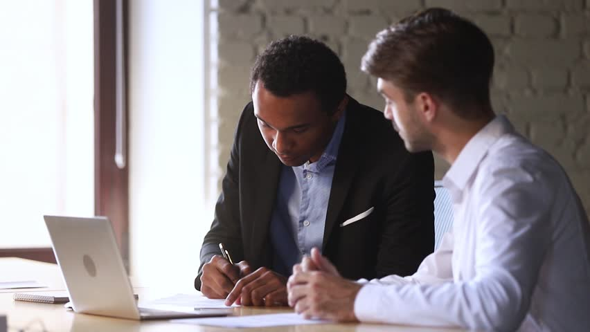 Happy african american client candidate handshake caucasian manager sign contract at business meeting get hired or buy services take bank loan, black customer and broker dealer shake hands make deal